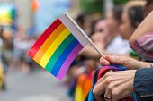 Gay Pride Parade spectator holding small gay rainbow flag during Toronto Pride Parade in 2017 poster