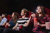 Low angle shot of happy young people smiling enjoying watching a movie at the cinema comedy premiere film spectators audience emotions positivity entertain concept. poster