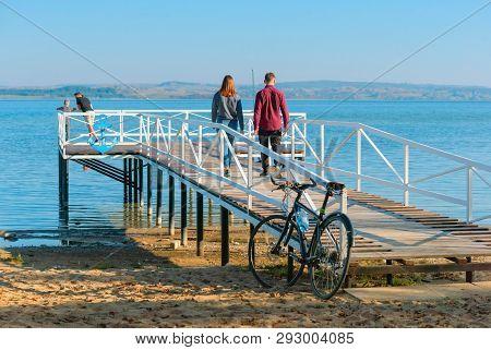 Wooden Pier On The Lake, Girl And Boy Walking On The Pier, Vishtynets Lake, Kaliningrad Region, Russ