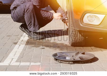 Man Picks Up Car Jack To Change Tire. Car Tires And Wheels With Wheels. Car Service. Change A Flat C