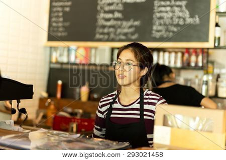 Asian Girl With Glasses Waitress Wearing Apron Standing In Coffee Shop.
