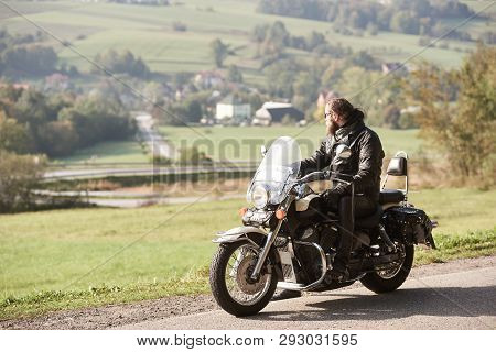 Long-haired Biker In Sunglasses And Black Leather Clothing Riding Modern Cruiser Motorcycle Along Su