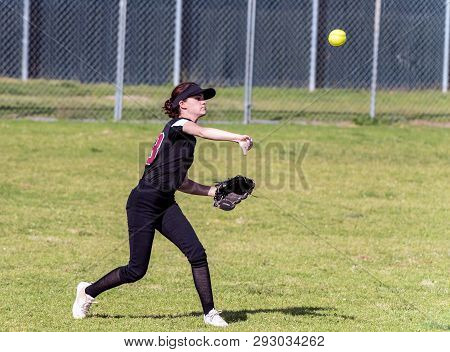 Skilled Teenage Softball Player Releasing A Quick Throw After Making A Defensive Catch In The Outfie