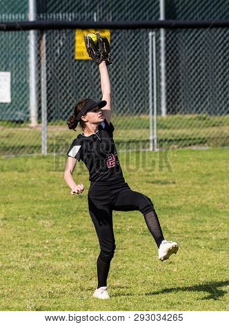 Skilled Teenage Softball Player Hanging On To Ball With Finger Tips After Making A Defensive Catch I