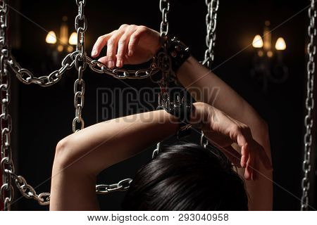 Hands Of Woman In Handcuffs Between Chains In Dark