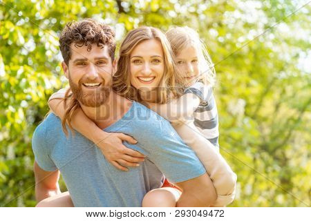 Strong and reliable man supporting his family by carrying wife and son piggyback