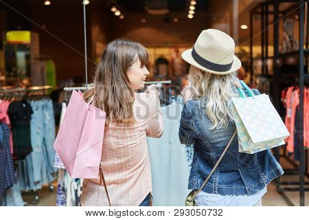 Young women buy clothes in front of a fashion shop in shopping mall
