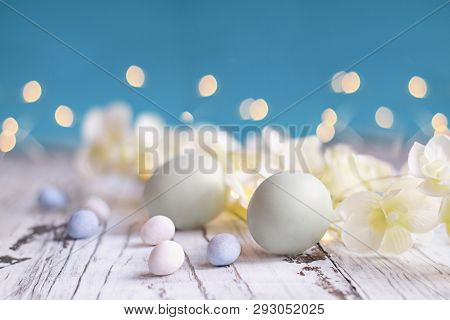 Natural Colored Easter Eggs, Malt Candy Covered Chocolate Eggs, And Flower Blossoms Over A Rustic Wh