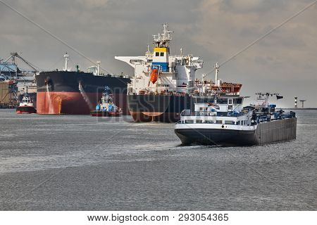 Ship traffic in the busy Port of Rotterdam, large crude oil tanker ship coming into port