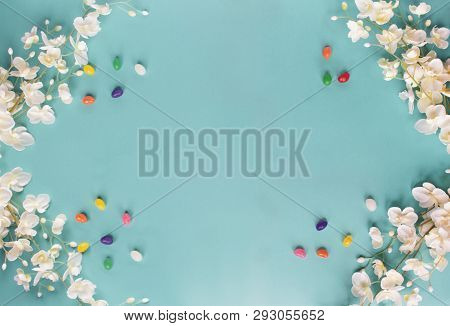 Jelly Beans And Spring Flowers Over A Teal / Blue Background With Room For Copy Space. Image Shot Fr