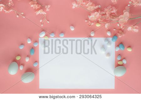 Pastel Easter Eggs, Malt Candy Covered Chocolate Eggs, And Flower Blossoms Over A Coral Colored Back