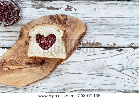 Top View Of Homemade Peanut Butter And Jelly Sandwich Over A Cutting Board On A White Rustic White W