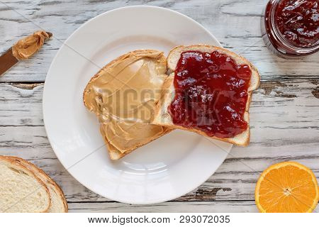 Top View Of Open Face Homemade Peanut Butter And Strawberry Jelly Sandwich On Oat Bread, Over A Whit