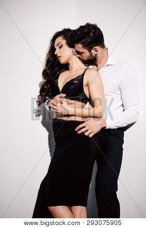 Handsome Man Kissing Neck Of Beautiful Woman In Black Dress On White