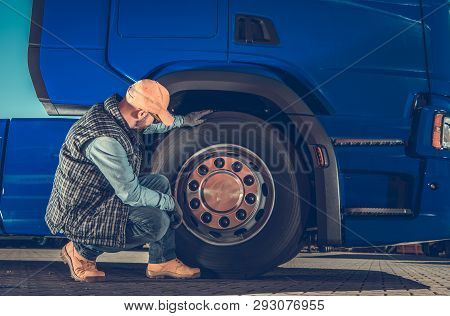 Caucasian Driver Checking Semi Truck Wheels Looking For Potential Issues. Transportation Industry Sa