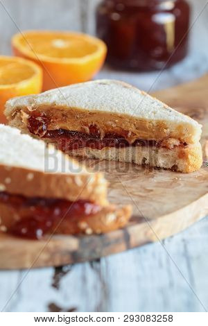 Homemade Sliced Peanut Butter And Jelly Sandwich On Oat Bread, Over A Rustic Wooden Background Ready