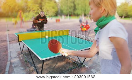 Group Of Happy Young Friends, Girl And Boy, Playing Ping Pong Table Tennis With Ball Outdoors. Conce