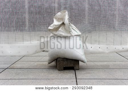 White Plastic Bag Filled With Sand And Used As A Weight On The Outdoor Reparation Spot. Reparation W