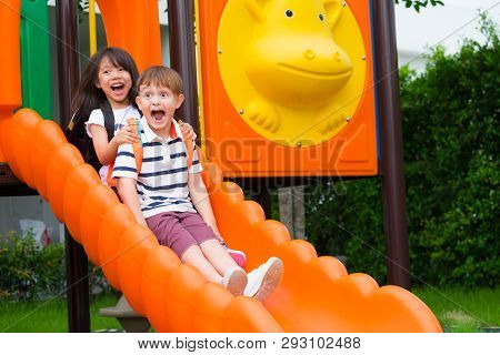 Two Kids Friends Having Fun To Play Together On Children's Slide At School Playground,back To School