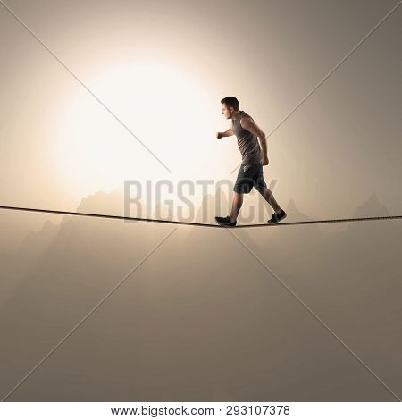 Man With A Walking Careless On A Rope At High Altitude.