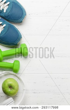 Fitness concept. Dumbbells, sneakers, headphones and apple on wooden background. Top view with space for your sport shedule text