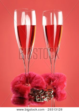 Two wine glasses and pink furry handcuffs conceptual still life isolated on red background