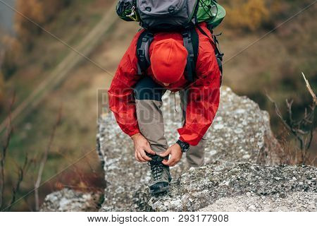 Caucasian Young Hiker Man Hiking In Mountains Dressed In Red Clothes Exploring New Places. Traveler