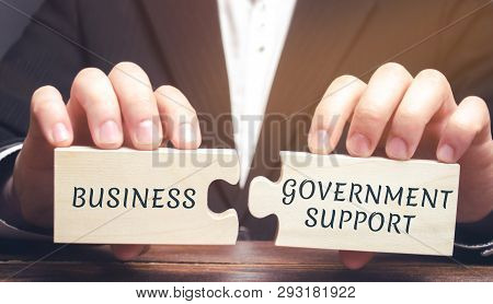 Businessman Collects Puzzles With The Words Business And Government Support. Tax Relief. Protection