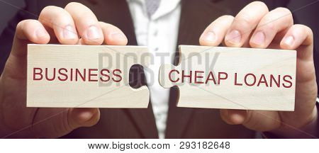 Businessman Collects Wooden Puzzles With The Words Business And Cheap Loans. Cheap And Affordable Lo