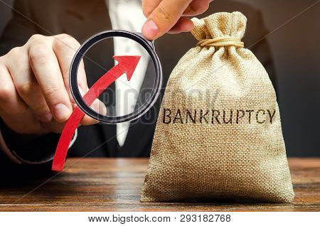 A Bag With The Word Bankruptcy And An Up Arrow In The Hands Of A Businessman. The High Level Of Bank