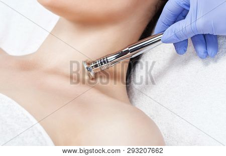 poster of The cosmetologist makes the procedure Microdermabrasion of skin of a beautiful, young woman in a beauty salon.Cosmetology and professional skin care.