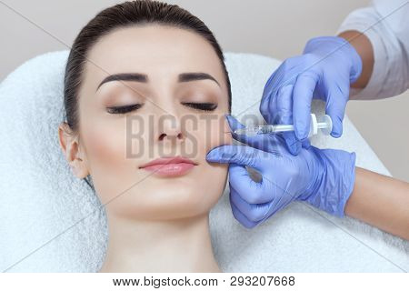 The cosmetologist makes the procedure Microdermabrasion of skin of a beautiful, young woman in a beauty salon.Cosmetology and professional skin care. poster