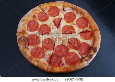 Pepperoni Pizza Italian Fast Food Served On Plate Isolated On Empty Black Wooden Table, Top View Fro
