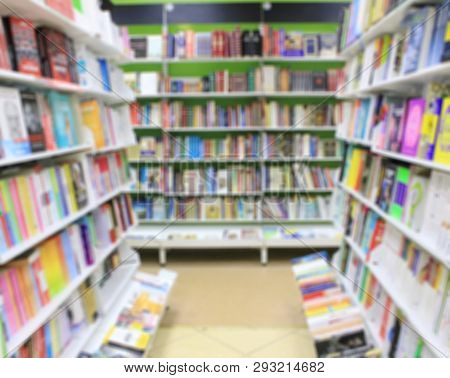 Bookstore Aisle Blurred Background With Books In Row On Shelves At Book Shop Interior. Colorful Blur
