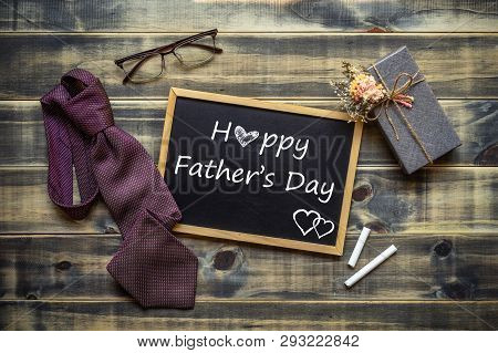 Happy Father's Day Concept. Flat Lay Image Of Gift Box, Necktie, Glasses And Chalkboard With Happy F