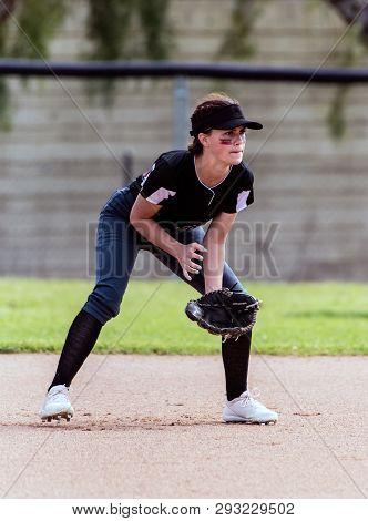Alert Female Softball Infielder Crouched Down Into Ready Position And Prepared For The Ball.