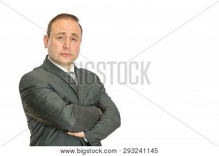A Perplexed-looking, Stern Businessman With Crossed Arms On A White Background With Copy Space.