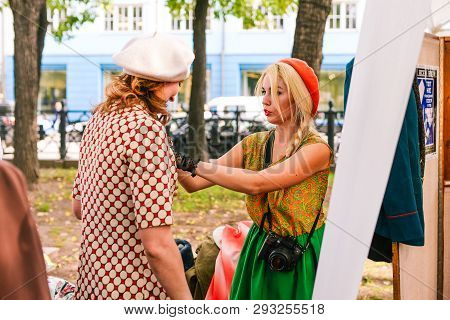 Russia, City Moscow - September 6, 2014: A Young Girl Photographer Dresses Up A Woman To Take A Phot