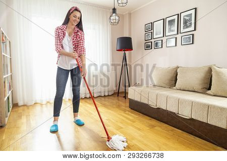 Woman holding a floor wiper and wiping floor, doing home chores and keeping the daily home hygiene poster