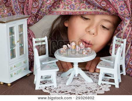 Little girl looking through a window into a doll's house like in alice in wonderland