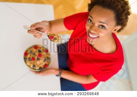 Young beautiful african american woman with afro hair eating healthy wholemeal cereals and berries as healthy breakfast