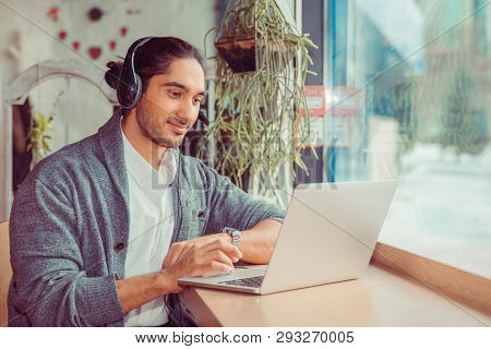 Image Of Smiling Bearded Young Man Student Sitting In Cafe While Using Laptop Computer And Listening