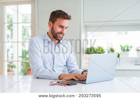 Handsome business man working using computer laptop with a happy face standing and smiling with a confident smile showing teeth