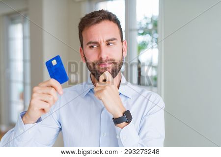 Handsome business man holding credit card serious face thinking about question, very confused idea