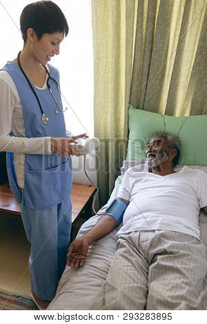 Front view of  Asian female nurse checking blood pressure of African-american senior male patient at retirement home