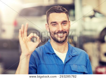 car service, repair, maintenance and people concept - happy smiling auto mechanic man or smith showing ok hand sign at workshop poster