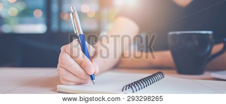 Woman Hand Is Writing On A Notebook With A Pen In Office.