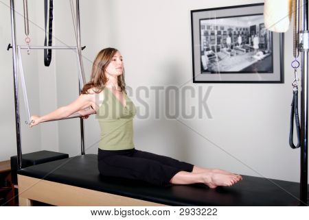 Horizontal image of a pretty young Pilates instructor working out on the Cadillac/Trap/Trapeze Table. poster