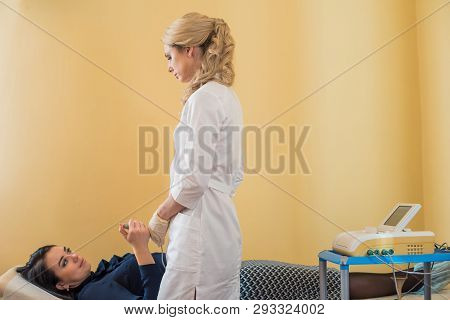 beautiful gynecologist examines the medical devices. The patient lies on the couch poster