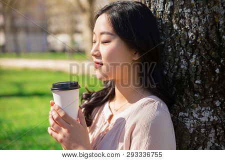 Tranquil Peaceful Girl Enjoying Takeaway Coffee In City Park. Closeup Of Young Asian Woman Leaning B
